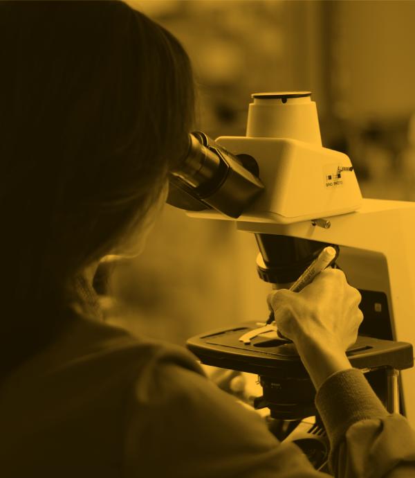 mujer scientifica mira por microscopio